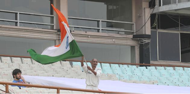 An Indian cricket fan waves tricolour as Indian team practices ahead of test match between India and West Indies starting on Nov 6 at Eden Gardens in Kolkata on Nov.5, 2013. (Photo: IANS)