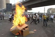 Egyptian protesters set cardboard boxes on fire during an anti-military demonstration outside the defense ministry