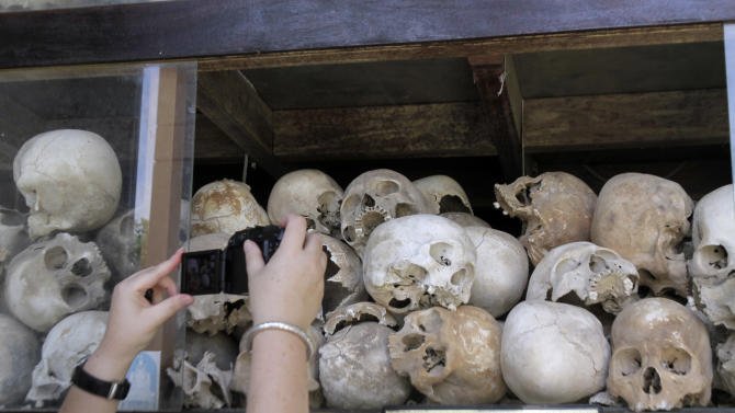 """CORRECTS SPELLING TO CHOEUNG EK THROUGHOUT - A tourist takes pictures of human skulls of Cambodian Khmer Rouge victims at Choeung Ek stupa, better known """"Killing field"""" on the outskirts of Phnom Penh, Cambodia, Sunday, Nov. 20, 2011. Some 200 Khmer Rouge victims on Sunday gathered at Choeung Ek for a Buddhist ceremony to dedicate to the souls of the dead before the start of the trial for former Khmer Rouge leaders. (AP Photo/Heng Sinith)"""