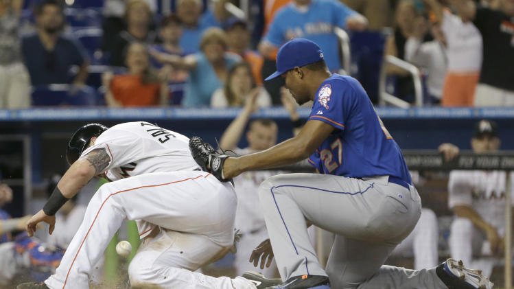 Miami Marlins' Jarrod Saltalamacchia, left, is safe at home as New York Mets relief pitcher Jeurys Familia drops the ball during the eighth inning of a baseball game, Monday, Sept. 1, 2014 in Miami. Familia had two throwing errors and a wild pitch, leading to three tiebreaking runs as the Marlins snapped a five-game losing streak to the Mets. The Marlins defeated the Mets 9-6. (AP Photo/Wilfredo Lee)
