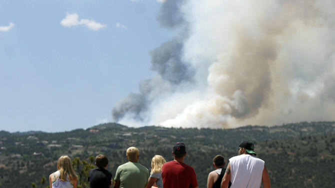 People watch as smoke billows from a wildfire west of Colorado Springs, Colo. on Saturday, June 23, 2012. The fire has grown to an estimated 600 acres and The Gazette reports authorities are evacuating the exclusive Cedar Heights neighborhood as well as the Garden of the Gods nature center. (AP Photo/Bryan Oller)