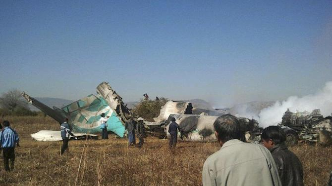 People gather at the wreckage of a Air Bagan Fokker-100 passenger jet that crashed in Heho