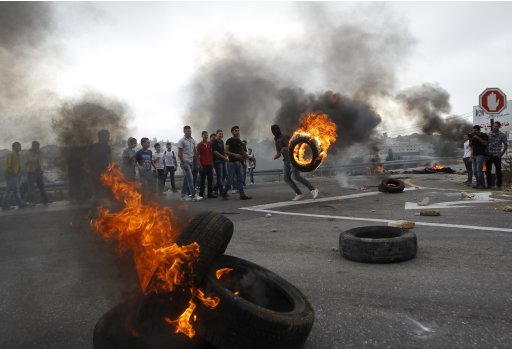 Palestinians stand near burning tyres during a protest near Ramallah