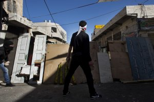A Palestinian stone-thrower stands behind a makeshift…