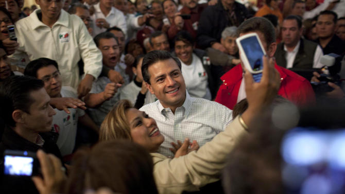 FILE - In this Feb. 9, 2012 file photo, Enrique Pena Nieto, presidential candidate for the Institutional Revolutionary Party (PRI) poses for photos with a supporter during a meeting with party members in Mexico City. The 2012 presidential race, which officially begins Friday March 30, 2012, is the PRI's race to lose. A dozen years ago, voters rose up and ended its 71-year iron grip on power, and many thought it had suffered its death knell. Elections are July 1. (AP Photo/Alexandre Meneghini, File)