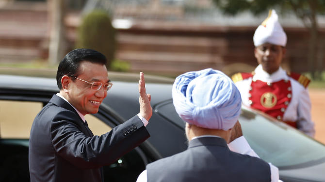 Chinese Premier Li Keqiang waves to Indian Prime Minister Manmohan Singh,  foreground, as he leaves the Indian Presidential Palace after his ceremonial reception in New Delhi, India, Monday, May 20, 2013. Just weeks after a tense border standoff, Li visited India on his first foreign three-day trip as the neighboring giants look to speed up efforts to settle a decades-old boundary dispute and boost economic ties. (AP Photo/Saurabh Das)