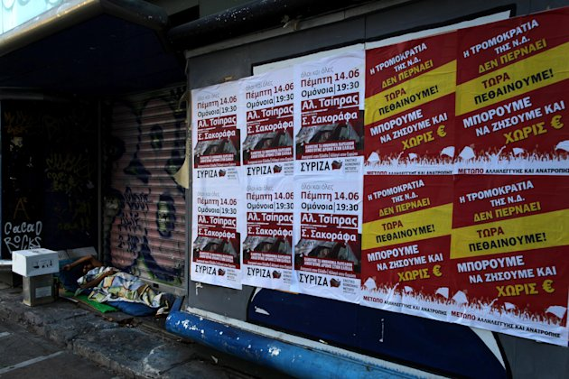 "A homeless man sleeps next  election posters, with far left political party, on right, reading ""we are dying now, we can live without Euro"", in central Athens, on Saturday, June 16, 2012.  Greeks cast"