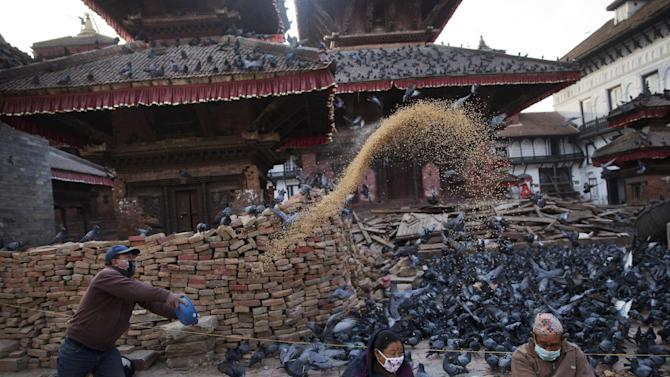 A Nepalese Hindu man feeds pigeons early morning at the Basantapur Durbar Square damaged during the April 25 earthquake in Kathmandu, Nepal, Tuesday, May 5, 2015. Nepal is one of the world's poorest nations, and its economy, largely based on tourism, has been crippled by the earthquake, which left thousands dead. (AP Photo/Bernat Amangue)