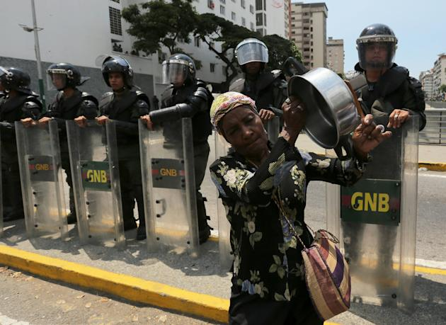A woman bangs on a pot in front of Bolivarian National Guardmen blocking a road to prevent demonstrators from arriving at the Food Ministry, in Caracas, Venezuela, Saturday, March 8, 2014. Venezuelans