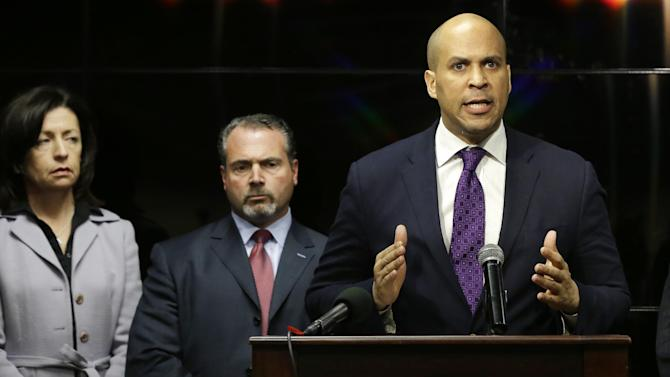 Newark Mayor Cory Booker responds at a news conference, Wednesday, Feb. 13, 2013 in Newark,  regarding a video that surfaced showing a naked young man being whipped because of his father's debt.  The men identified are 22-year-old Ahmad Holt, 31-year-old Raheem Clark and 23-year-old Jamaar Gray. Police say Holt administered the beating, using a belt provided by Clark. Charges include robbery and aggravated assault.   The video shows a 21-year-old man being forced to strip and then whipped with a belt, supposedly because his father owed someone $20. Subsequent to the police investigation, Nicole A. Smith was arrested for drug possession. (AP Photo/Mel Evans)
