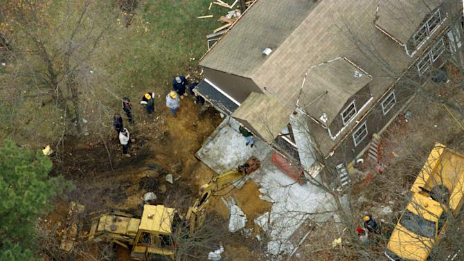 """FILE - In this Jan. 17, 1993 file photo, officials employ a backhoe to break up a slab of concrete that covers a subterranean room behind a carport at the home of John Esposito in Bay Shore, N.Y., where he held Katie Beers for 17 days. On the 20th anniversary of her ordeal, Beers has co-written a book with a television reporter who covered her kidnapping. """"Buried Memories: Katie Beers' Story"""" (Title Town Publishing) has a happy ending.  (AP Photo/Alex Brandon, File)"""