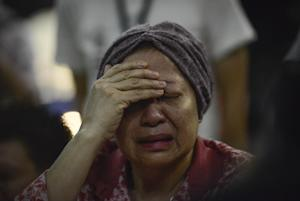 A woman reacts after hearing about the Malaysia Airlines …