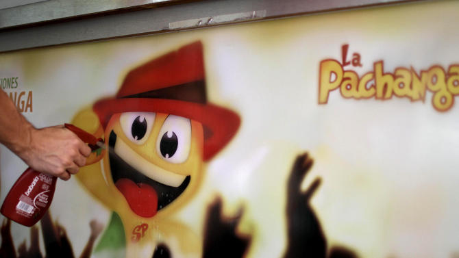 In this June 10, 2012 photo, design student Alejandro Perez sprays water on a advertisement sign promoting La Pachanga, a private cafeteria, preparing to attach it to the serving bar in Havana. Perez and a team of students helped design the cafeteria's mascot and ad campaign. For decades, Communist-run Cuba has essentially been free of commercial advertising. But it's a knotty problem for thousands of budding entrepreneurs who have embraced President Raul Castro's push for limited free-market reform. So they're turning to guerrilla marketing. (AP Photo/Franklin Reyes)