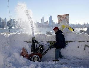 A resident removes snow away from the entrance to his …