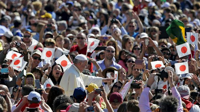 Pope Francis waves as he arrives to lead the general audience in St. Peter's Square at the Vatican