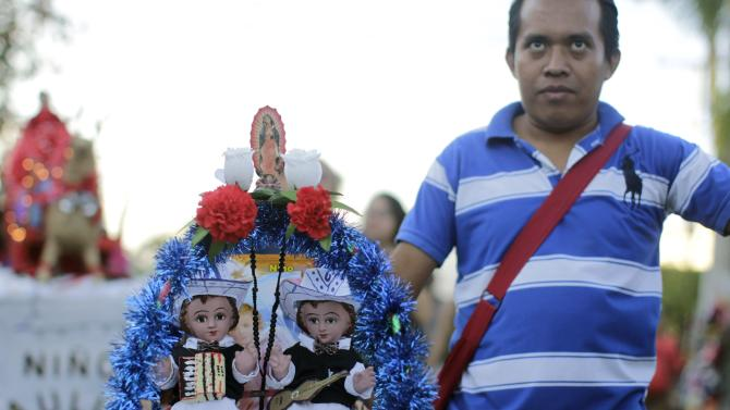 A Catholic man holds figurines of baby Jesus during a religious procession on Holy Innocents Day in Antiguo Cuscatlan