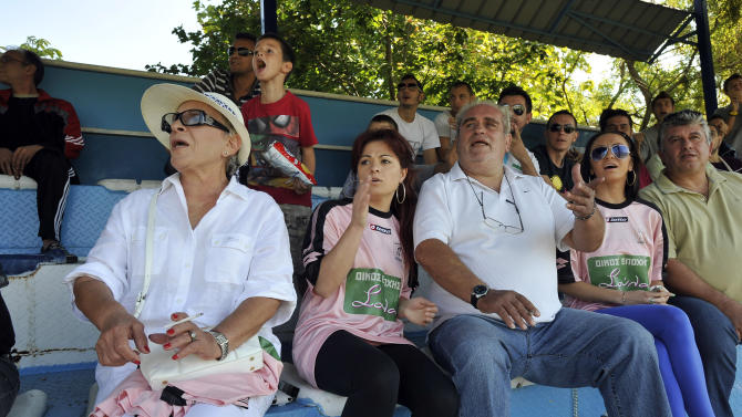 In this photo taken Sunday, Oct. 7, 2012, brothel owner Soula Alevridou, left, the benefactor of the Voukefalas amateur soccer team, reacts during a local championship match in the city of Larissa, central Greece.  A cash-strapped Greek soccer team has found a new way to pay the bills, with help from the world's oldest profession. Players are wearing bright pink practice jerseys emblazoned with the logos of the Villa Erotica and Soula's House of History, a pair of pastel-colored bordellos recruited to sponsor the team after drastic government spending cuts left the country's sports organizations facing ruin. One team took on a deal with a local funeral home and others have wooed kebab shops, a jam factory, and producers of Greece's trademark feta cheese. But the small amateur Voukefalas club which includes students, a bartender, waiters and pizza delivery drivers is getting the most attention for its flamboyant sponsors.  Logo on T-shirts translates to 'Soula's House of History'. (AP Photo/Nikolas Giakoumidis)