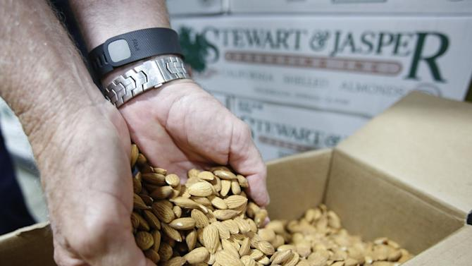 In this Tuesday, July 21, 2015 photo, Jim Jasper, owner of Stewart Jasper Orchards, displays a box of almonds that are ready for shipping at his processing plant in Newman, Calif.  Like many Central Valley growers, Jasper depends on water from pumped from the Sacramento San Joaquin River Delta to irrigate his crops. Jasper says the efforts to save the endangered Delta smelt, which has caused a reduction of irrigation water, is partly to blame for him pulling out 400 acres of almond trees because he couldn't get enough water. (AP Photo/Rich Pedroncelli)