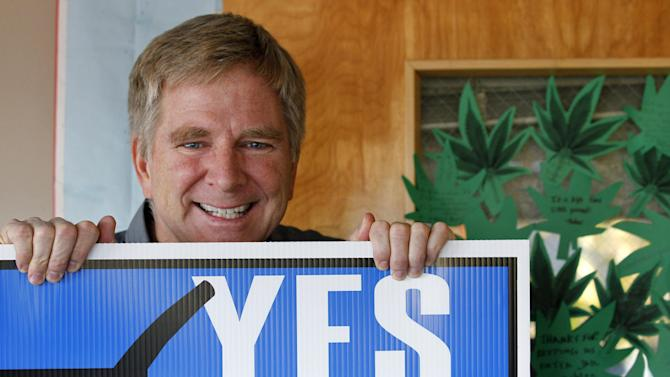 """In this Monday, Nov. 26, 2012 photo, travel guide author and marijuana legalization supporter Rick Steves holds a campaign sign in his office in Edmonds, Wash next to a door covered with marijuana leaf-shaped notes from his staff congratulating him on the passage of a referendum legalizing marijuana in the state. In the late-1980s heyday of the """"Just Say No"""" campaign, a man calling himself """"Jerry"""" appeared on a Seattle radio station's midday talk show, using a pseudonym because he was a businessman, afraid of what his customers would think if they heard him criticizing U.S. marijuana laws. A quarter century later, """"Jerry"""" had no problem using his real name - Rick Steves - as one of the main forces behind Washington's successful ballot measure to legalize, regulate and tax marijuana for adults over 21. (AP Photo/Elaine Thompson)"""
