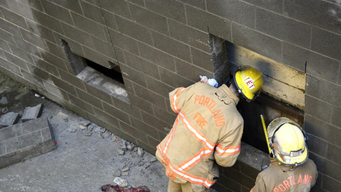 Portland firefighters Fred Williams, right, and Gary Fergus check one of two holes that were cut out to free a woman who fell part of the way down the 20-foot wall and got herself stuck between two buildings in Portland, Ore., Wednesday, Jan. 16, 2013.  The woman spent about four hours in a space less than a foot wide Wednesday morning. In addition to the an air bag, rescuers also cut a hole and used a soapy substance to lubricate the concrete block walls to remove the woman.(AP Photo/Don Ryan)