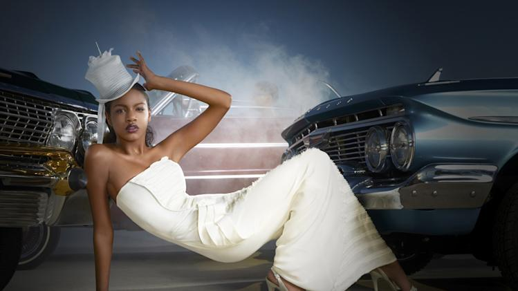 "Eboni models a British couture hat while posing with a vintage American car on ""America's Next Top Model."""