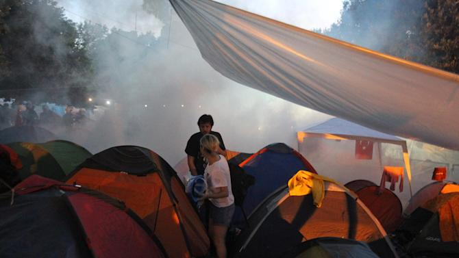Police throw tear gas as protestors stand among tents during an operation to evacuate the Gezi Park of Taksim Square in Istanbul, Saturday, June 15, 2013. Protesters will press on with their sit-in at an Istanbul park, an activist said Saturday, defying government appeals and a warning from Prime Minister Recep Tayyip Erdogan for the two-week standoff that has fanned nationwide demonstrations to end. (AP Photo/Thanassis Stavrakis)