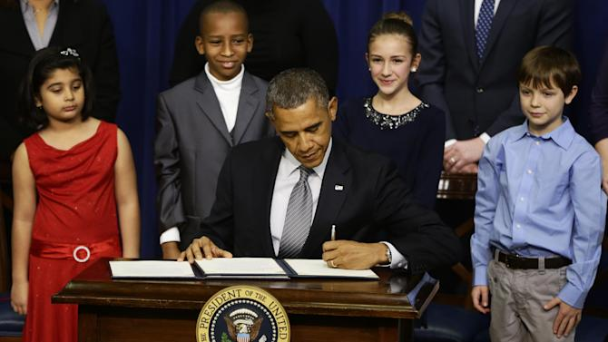 From left to right: Hinna Zeejah, 8, Taejah Goode, 10, Julia Stokes, 11, and Grant Fritz, 8, who wrote letters to President Barack Obama about the school shooting in Newtown, Conn., watch as Obama signs executive orders outlining proposals to reduce gun violence, Wednesday, Jan. 16, 2013, in the South Court Auditorium at the White House in Washington. (AP Photo/Charles Dharapak)