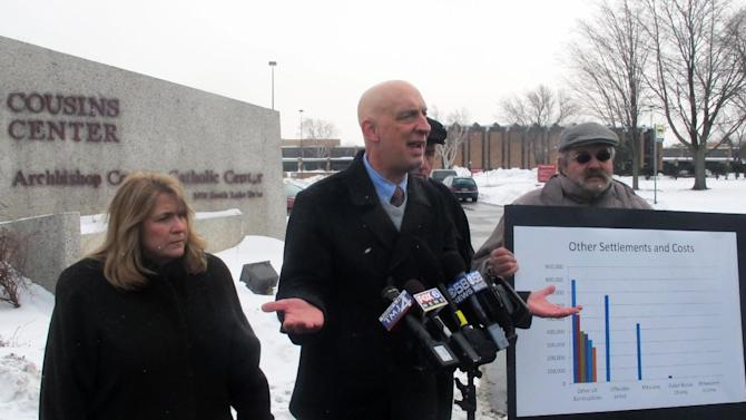 Survivors of clergy sexual abuse Monica Barrett, left, Peter Isely, center, and Michael Sneesby speak to reporters on Wednesday, Feb. 12, 2014, outside the headquarters of the Milwaukee Archdiocese. The archdiocese says it's prepared to set aside $4 million in its bankruptcy reorganization plan to compensate victims of clergy sexual abuse, an amount survivors called insulting. (AP Photo/Dinesh Ramde)