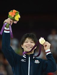 Japan's gymnast Kohei Uchimura celebrates on the podium with his gold medal after winning the men's individual all-around competition of the artistic gymnastics event of the London Olympic Games on August 1, 2012 at the 02 North Greenwich Arena in London. Japanese superstar Kohei Uchimura romped to the individual all-around gymnastics title to claim his first Olympic gold medal while Germany's Marcel Nguyen took the silver medal, with Danell Leyva of the United States winning the bronze.    AFP PHOTO / EMMANUEL DUNAND