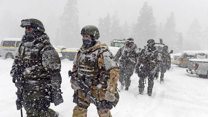 A San Bernardino County Sheriff SWAT team returns to the command post at Bear Mountain near Big Bear Lake, Calif. after searching for Christopher Jordan Dorner on Friday, Feb. 8, 2013. Search conditions have been hampered by a heavy winter storm in the area. Dorner, a former Los Angeles police officer, is accused of carrying out a killing spree because he felt he was unfairly fired from his job. (AP Photo/The Inland Valley Daily Bulletin, Will Lester, Pool)