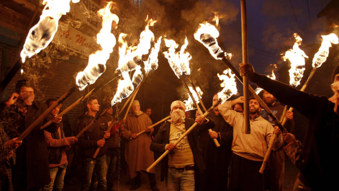 Activists and supporters of Jammu and Kashmir Liberation Front (JKLF) hold torches as they participate in a protest march to mark International Human Rights Day in Srinagar, India, Monday, Dec. 10, 2012. More than 68,000 people, mostly civilians, have been killed since the outbreak of the insurgency in the region in 1989. Pakistan, Kashmiri separatist leaders and human rights groups have been demanding a reduction in India's military presence in Kashmir. (AP Photo/Mukhtar Khan)