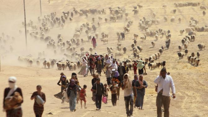 Displaced people from minority Yazidi sect, fleeing violence from forces loyal to ISIL in Sinjar town, walk toward the Syrian border, on outskirts of Mount Sinjar.