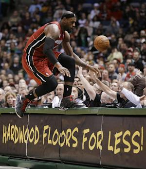 Miami Heat's LeBron James jumps onto a table while trying to save a ball going out of bounds against the Milwaukee Bucks in the second half of an NBA basketball game Friday, March, 15, 2013, in Milwaukee. (AP Photo/Jeffrey Phelps)
