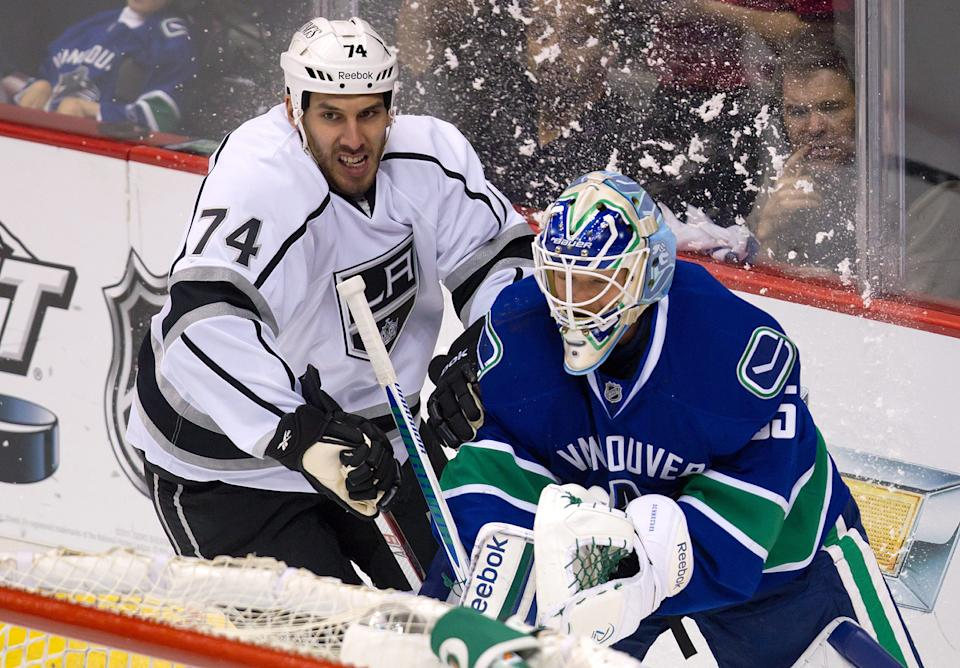 Los Angeles Kings' Dwight King, left, challenges Vancouver Canucks' goalie Cory Schneider as he plays the puck behind his net during the first period of game 5 of an NHL Western Conference quarterfinal Stanley Cup playoff hockey series in Vancouver, British Columbia on Sunday April 22, 2012.  (AP Photo/The Canadian Press, Darryl Dyck)