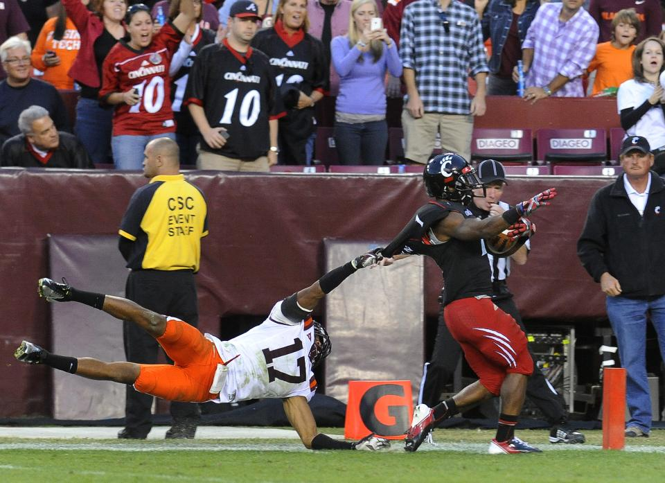 Cincinnati running back Ralph David Abernathy (1) races into the end zone, dragging Virginia Tech cornerback Kyle Fuller during the fourth quarter of an NCAA college football game, Saturday, Sept. 29, 2012, in Landover, Md. Cincinnati defeated Virginia Tech 27-24. (AP Photo/Richard A. Lipski)
