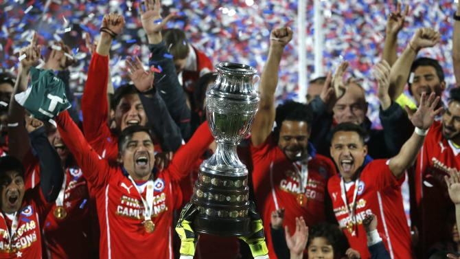 Chile players celebrate with the Copa America trophy after they defeated Argentina in their Copa America 2015 final soccer match at the National Stadium in Santiago