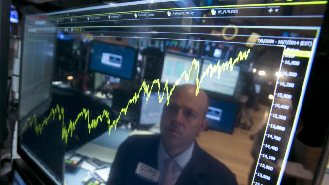 FILE - In this July 3, 2014 file photo, specialist Jay Woods is reflected in a screen at his post that shows five years of the Dow Jones industrial average, on the floor of the New York Stock Exchange. The Dow Jones industrial average jumped above 17,000 for the first time that day. The Standard & Poor's 500 index climbed about 13 percent in 2014, hitting a record high a remarkable 51 times. (AP Photo/Richard Drew, File)