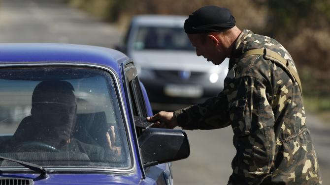 A Ukrainian serviceman inspects a car at a checkpoint near the town of Horlivka