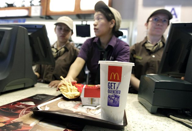 McDonald's employees serve a meal containing a large soda, Tuesday, June 12, 2012, in New York. Mayor Michael Bloomberg's proposal to ban large sugary drinks from New York City eateries is moving forw