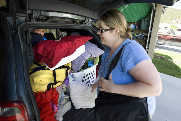 Lisel Christiansen packs her van with items as she prepares to leave her home in Eagle Mountain, Utah Friday, June 22, 2012. Officials say about 250 homes are being evacuated after high winds kicked up a fire near a northern Utah dump. Fire officials say the blaze just west of the Saratoga Springs landfill has burned more than 750 acres. (AP Photo/The Salt Lake Tribune, Paul Fraughton)