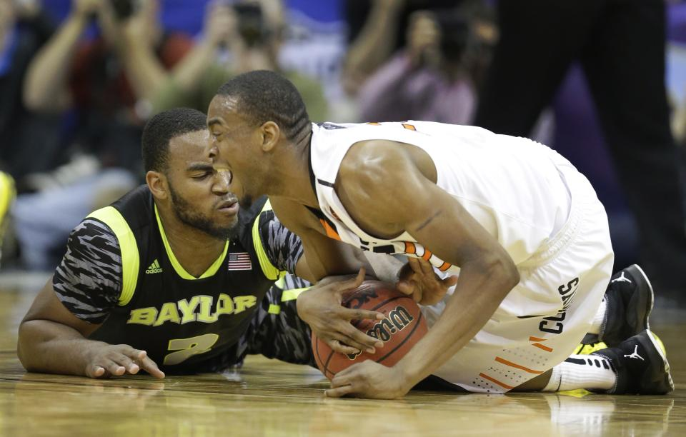 Oklahoma State guard Markel Brown, right, and Baylor forward Rico Gathers (2) battle on the floor during the first half of an NCAA college basketball game in the Big 12 tournament on Thursday, March 14, 2013, in Kansas City, Mo. (AP Photo/Orlin Wagner)