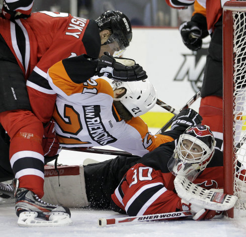 New Jersey Devils goalie Martin Brodeur, right, makes a save as teammate Alexei Ponikarovsky, left, of Ukraine, collides with Philadelphia Flyers&#39; James van Riemsdyk during the first period of Game 4 of a second-round NHL hockey Stanley Cup playoff series, Sunday, May 6, 2012, in Newark, N.J. (AP Photo/Julio Cortez)