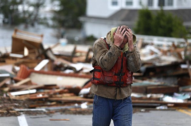 Brian Hajeski, 41, of Brick, N.J., reacts after looking at debris of a home that washed up on to the Mantoloking Bridge the morning after superstorm Sandy rolled through, Tuesday, Oct. 30, 2012, in Ma