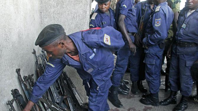 A Congo government policeman hands in his weapon to M23 rebels during an M23 rally in Goma, Congo, Wednesday, Nov. 21, 2012. A rebel group believed to be backed by Rwanda seized the strategic, provincial capital of Goma in eastern Congo on Tuesday, home to more than 1 million people as well as an international airport in a development that threatens to spark a new, regional war, officials and witnesses said. (AP Photo/Melanie Gouby)