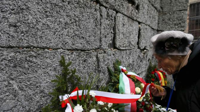 A survivor adjusts a ribbon on a wreath at the 'Wall of Death' in the former Nazi German concentration and extermination camp Auschwitz in Oswiecim