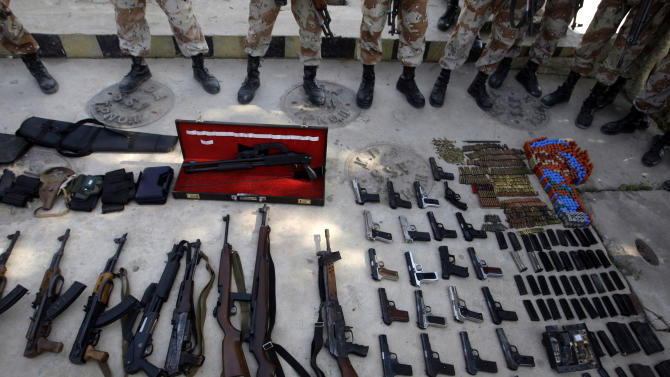 Pakistani paramilitary forces display weapons reportedly confiscated from outlaws during a crackdown operation, in Karachi, Pakistan, Monday, Dec. 10, 2012. Gunmen attacked a checkpoint manned by paramilitary forces on the outskirts of the southern city of Karachi, killing soldiers, police said. (AP Photo/Shakil Adil)