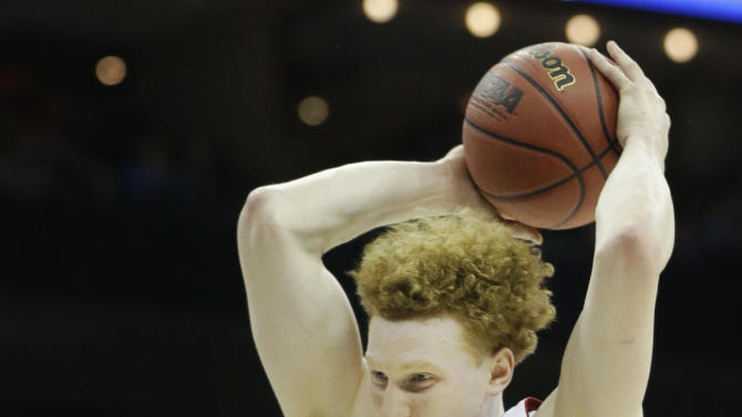Wisconsin forward Mike Bruesewitz (31) rebounds over Mississippi forward Reginald Buckner (23) during the first half of a second-round game in the NCAA college basketball tournament at the Sprint Center in Kansas City, Mo., Friday, March 22, 2013. (AP Photo/Orlin Wagner)