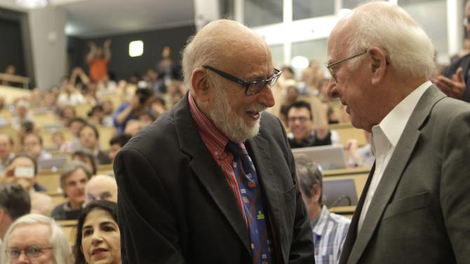 "British physicist Peter Higgs, right,  shakes hands with Belgian  physist Francois Englert  prior to a  scientific seminar to deliver the latest update in the search for the Higgs boson at the European Organization for Nuclear Research (CERN) in Meyrin near Geneva, Switzerland, Wednesday, July 4, 2012. The head of the world's biggest atom smasher is claiming discovery of a new particle that he says is consistent with the long-sought Higgs boson known popularly as the ""God particle.""  Rolf Heuer, director of the European Center for Nuclear Research, or CERN, says ""we have a discovery"" of a new subatomic particle, a boson, that is ""consistent with a Higgs boson.""  He spoke after two independent teams at CERN said they have both ""observed"" a new boson that looks just like the one believed to give all matter in the universe size and shape.  (AP Photo//Denis Balibouse,Pool)"
