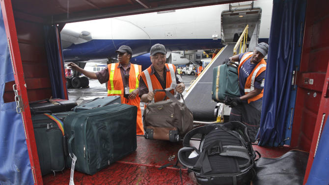 FILE-In this Wednesday, Aug. 1 2012 file photo, Delta Air Lines ramp agents unload bags from a flight arriving at JFK International airport in New York. U.S. airlines collected more than $1.7 billion in baggage fees during the first half of the year, the largest amount ever collected in that six-month period. Delta Air Lines Inc. once again claimed the title as the airline collecting the most in baggage fees: nearly $430 million from January through June. The slightly larger United Airlines, part of United Continental Holdings Inc.,  followed with $351 million in bag fees, according to a report from the Bureau of Transportation statistics released Tuesday. (AP Photo/Mary Altaffer, File)