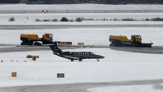 Snow ploughs remove snow from the tarmac at Manchester Airport in Manchester